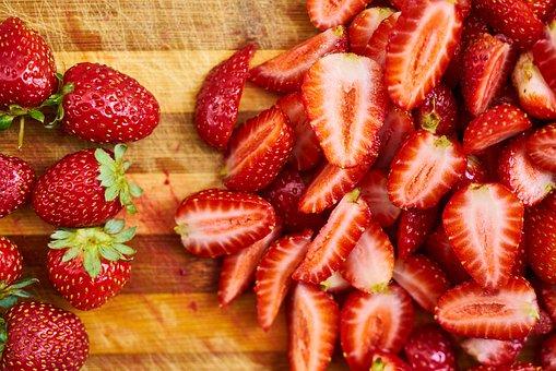 Целые ягоды клубники и разрезанная