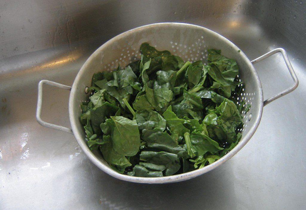 Помытые листья шпината в дуршлаге